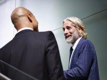 Dois executivos empresariais que falam quando escadas de ascensão fotos de stock