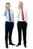 Dois executivos masculinos que falam no telefone celular foto de stock royalty free