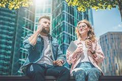 Dois executivos novos estão sentando-se na rua No fundo, arranha-céus no foco macio Dia ensolarado do verão foto de stock royalty free
