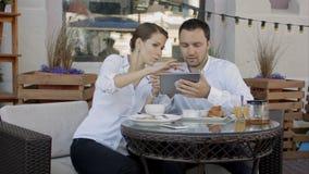 Dois executivos novos que usam a tabuleta digital em uma reunião na cafetaria fotografia de stock