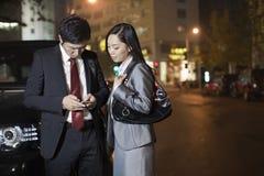 Dois executivos que olham o telefone celular Fotografia de Stock