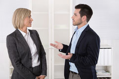 Dois executivos que trabalham em uma equipe que fala junto no de Fotografia de Stock Royalty Free