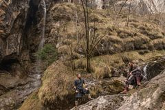Dois exploradores de Viking descansam nas rochas ao lado de uma cachoeira no th fotografia de stock