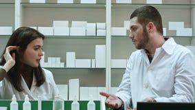 Dois farmacêuticos adultos que têm o conflito, discutindo problemas na farmácia video estoque