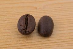 Dois feijões de café differen dentro posições sobre a tabela de madeira fotos de stock