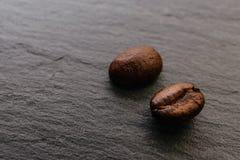 Dois feijões de café em uma superfície áspera Imagem de Stock