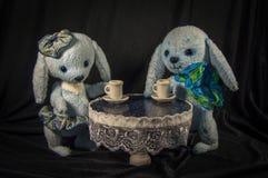 Dois filhotes de lebre das bonecas que bebem o chá na tabela Foto de Stock