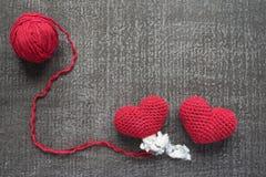 Dois fizeram crochê corações vermelhos em uma placa do grunge Fotografia de Stock Royalty Free