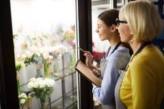 Dois floristas fêmeas que escolhem flores imagens de stock