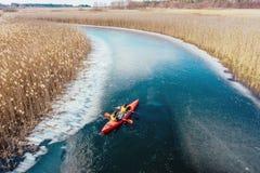 Dois flutuadores atl?ticos do homem em um barco vermelho no rio imagem de stock