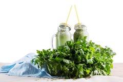 Dois frascos de pedreiro de batidos verdes das ervas e do vegetal, isolados em um fundo branco Conceito da dieta e da aptidão Fotografia de Stock