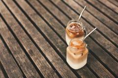 Dois frascos de vidro do caf? de gelo na tabela de madeira com palhas do metal fotografia de stock royalty free