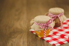 Dois frascos do mel e dos favos de mel isolados no branco Imagens de Stock