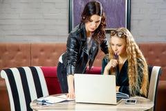 Dois freelancers estão discutindo projetos novos ao sentar-se em um café com os dispositivos eletrónicos imagens de stock royalty free
