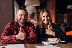 Dois freelancers felizes sorriem na câmera no dedo do café acima, bom trabalho Fotos de Stock Royalty Free
