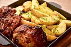 Dois fritaram partes de carne e de batatas com verdes em um prato fotos de stock royalty free