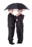 Dois gêmeos bonitos dos rapazes pequenos em ternos de negócio com isola do guarda-chuva Imagem de Stock