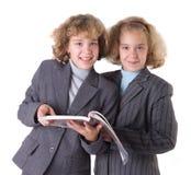 Dois gêmeos com livro de texto Fotos de Stock Royalty Free
