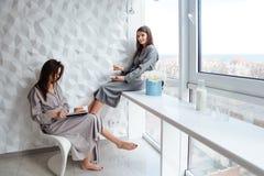 Dois gêmeos das irmãs que têm o café da manhã e o livro de leitura perto da janela Foto de Stock