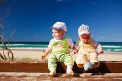 Dois gêmeos do irmão gémeo do bebê que sentam-se em uma praia Imagens de Stock Royalty Free