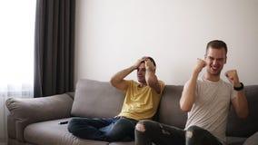 Dois gamers que sentam-se no sofá após a terminação jogando o jogo Um deles é o vencedor e apreciação disso que feelling vídeos de arquivo