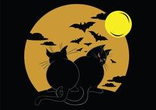 Dois gatos pretos com bastões e lua Imagem de Stock