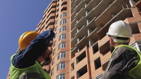 Dois gerentes da construção nos capacetes com uma barba e um bigode para discutir detalhes da construção no canteiro de obras 4K filme