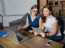 Dois gerentes das mulheres que preparam-se à conferência usando o rede-livro e a almofada de toque imagens de stock royalty free