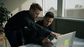 Dois gerentes masculinos que trabalham junto no escritório moderno video estoque
