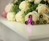 Dois giradores da inquietação cor-de-rosa e brinquedos verdes na prateleira branca com as flores no close up do fundo Fotografia de Stock