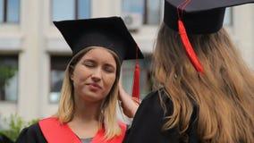 Dois graduados novos da fêmea que discutem os planos futuros após a cerimônia de graduação filme