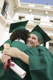 Dois graduados que abraçam a universidade exterior fotografia de stock royalty free