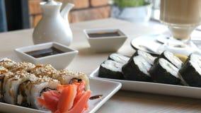 Dois grupos de rolos de sushi em um café à moda, belamente decorado Culinária japonesa do restaurante na tabela ao lado do sushi video estoque