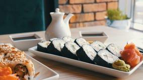 Dois grupos de rolos de sushi em um café à moda, belamente decorado Culinária japonesa do restaurante na tabela ao lado do sushi vídeos de arquivo
