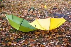 Dois guarda-chuvas encontram-se na grama entre as folhas de outono Passeio foto de stock