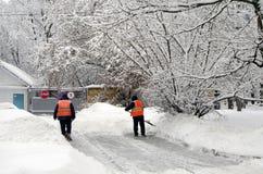 Dois guarda de serviço limpam a neve após a queda de neve Moscou Rússia no 4 de fevereiro de 2018 Fotos de Stock