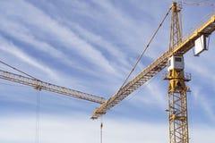 Dois guindastes de construção que encontram-se contra o céu azul imagens de stock