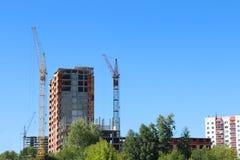 Dois guindastes do hig e construções de tijolo sob a construção Imagem de Stock