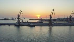 Dois guindastes do porto com o sol que aumenta in-between imagem de stock