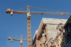 Dois guindastes e casas de construção sob a construção Foto de Stock