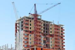 Dois guindastes e construções de tijolo altos sob a construção Fotos de Stock Royalty Free