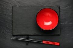 Dois hashis e placa vermelha no fundo de pedra preto com copyspace Foto de Stock