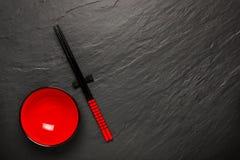 Dois hashis e placa vermelha no fundo de pedra preto com copyspace Imagem de Stock Royalty Free