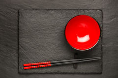 Dois hashis e placa vermelha no fundo de pedra preto com copyspace Fotografia de Stock Royalty Free