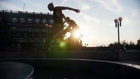 Dois homens acrobáticos que correm acima e salto sobre a fonte - por do sol filme