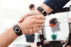 Dois homens agitam as mãos no laboratório da engenharia Atrás deles é uma impressora 3d Foto de Stock