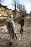 Dois homens armados que olham ao redor na vila Fotografia de Stock