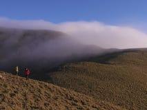 Dois homens asiáticos que estão no monte das montanhas, e lá são um torward de derivação da névoa grossa onde estejam fotos de stock royalty free