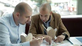 Dois homens calvos discutem o negócio no almoço em um café, comendo macarronetes Alimento chinês, centro de negócios vídeos de arquivo