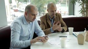 Dois homens calvos no almoço em um café pelos macarronetes bebendo do café e comer da janela que discutem o negócio Trabalho, tel video estoque